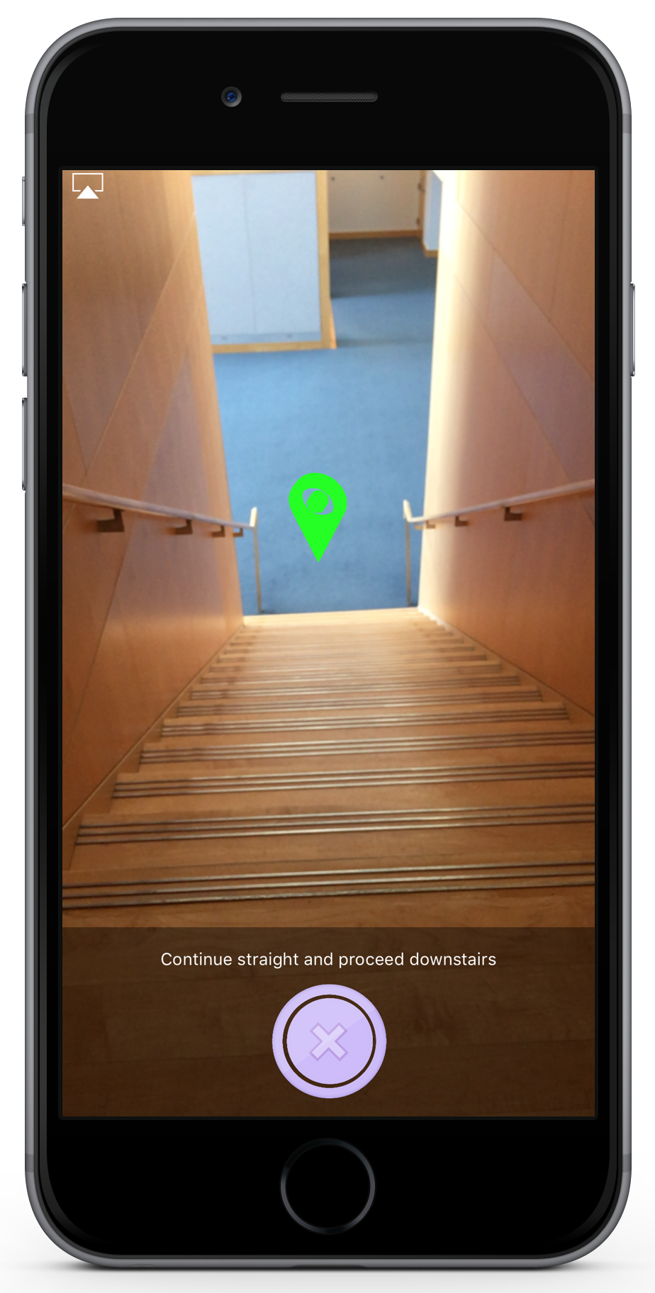 an image of the app in navigation mode.  The image shows a waypoint overlaid on the image at the bottom of a staircase.  The text says 'Continue straight and proceed downstairs.'