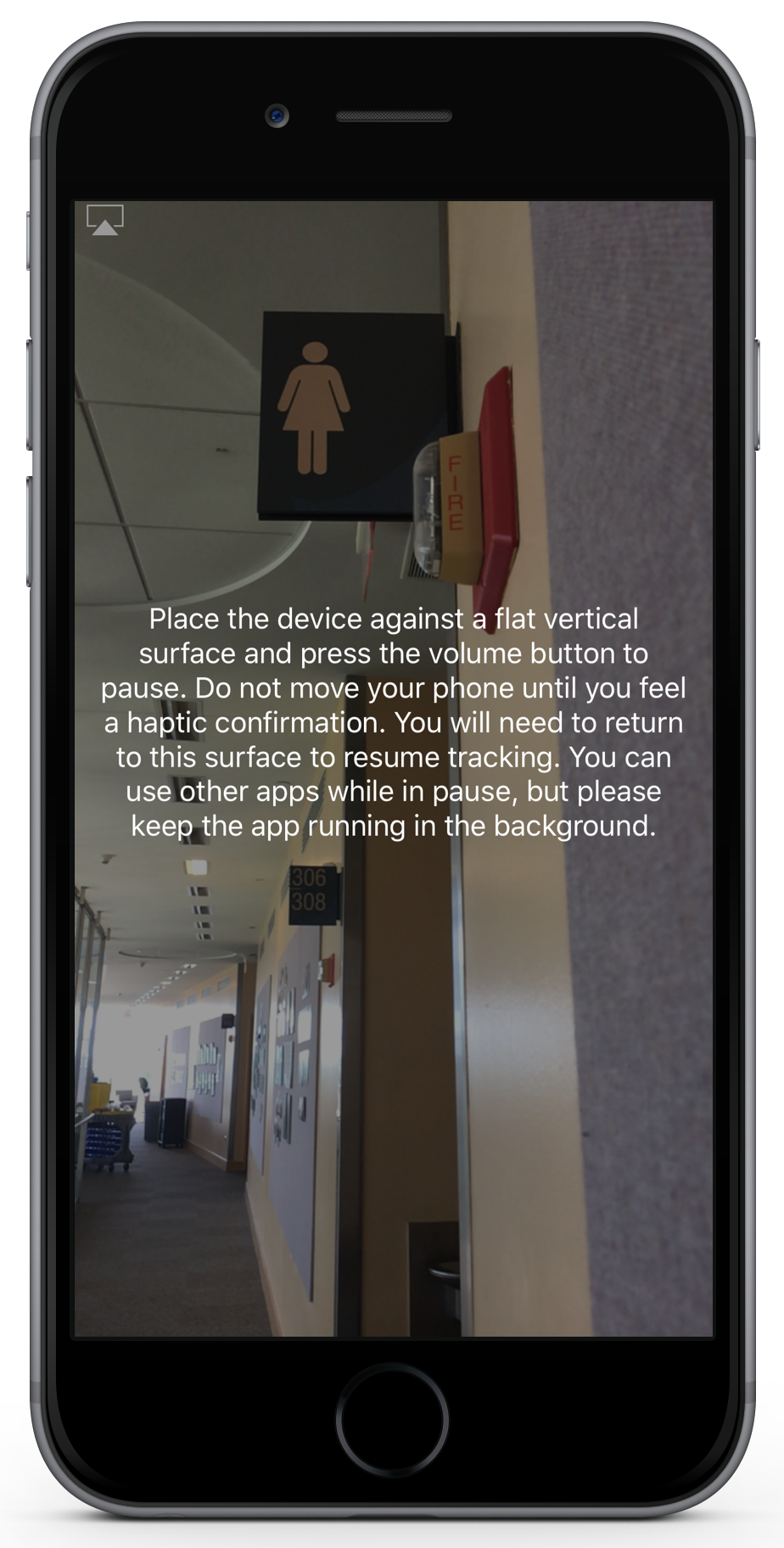 "a screenshot of the pause feature.  The image shows a hallway.  In the center of the image is text that says ""Place the device against a flat vertical surface and press the volume button to pause.  Do not move your phone until you feel a haptic confirmation.  You will need to return to this surface to resume tracking.  You can use other apps while in pause, but please keep the app running in the background."""